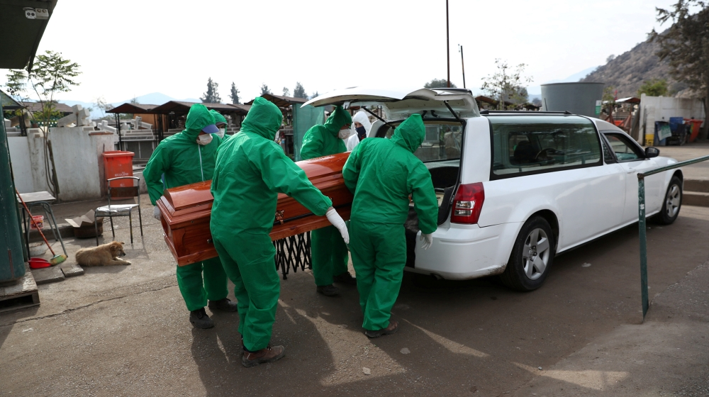 Cemetery workers carry the casket of 68-year-old Jose, who died of the coronavirus disease (COVID-19), during his funeral in Colina area, Santiago, Chile June 19, 2020. According to his granddaughter