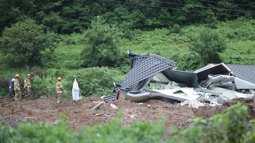 epa08591102 Rescue workers search for a person trapped in the debris of a landslide at a village in Gokseong, South Korea, 08 August 2020. Four people were dead and one missing after the landslide tri