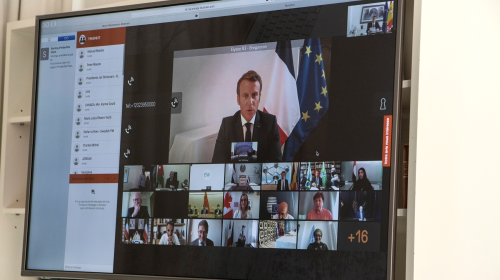 A handout photo made available by the office of the prime minister of Spain (La Moncloa) shows French President Emmanuel Macron (on screen) participates via a video connection with world leaders about