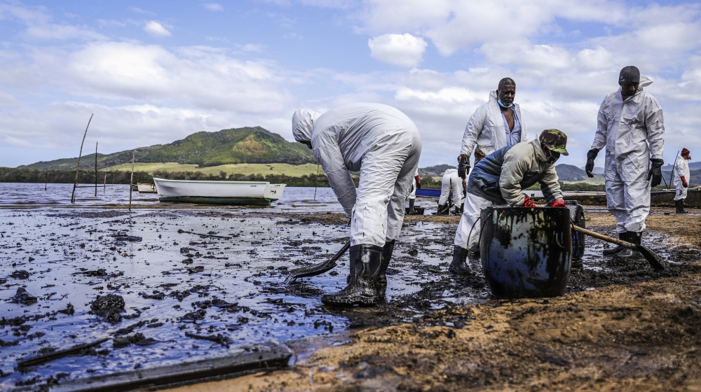 People scoop leaked oil from the vessel MV Wakashio, belonging to a Japanese company but Panamanian-flagged, that ran aground and caused oil leakage near Blue bay Marine Park in southeast Mauritius on