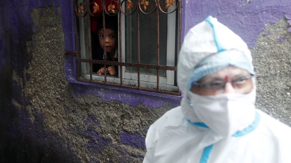 A boy watches a health worker in personal protective equipment (PPE) as she walks past a house during a check up campaign for the coronavirus disease (COVID-19), in Mumbai