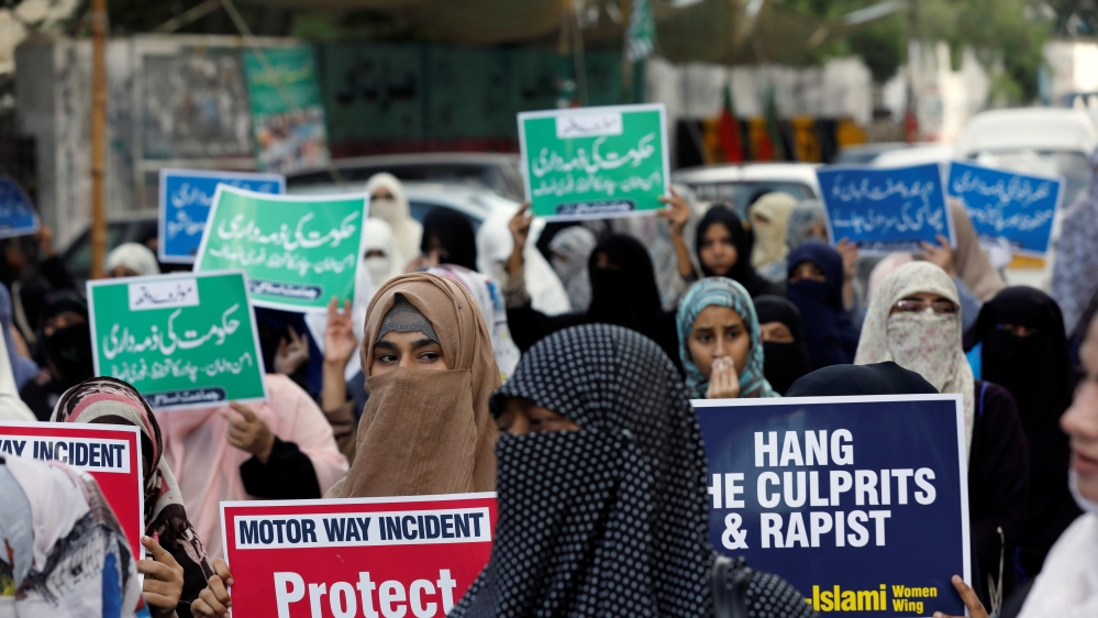 People carry signs to condemn the violence against women and girls, during a demonstration in Karachi