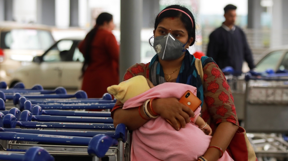 A passenger wearing a protective mask holds a baby as she waits outside an airport following an outbreak of the coronavirus disease (COVID-19), in New Delhi, India, March 14, 2020. REUTERS/Anushree Fa