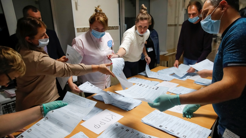 Members of a local electoral commission count ballots at a polling station after polls closed for the municipal elections in Tomsk