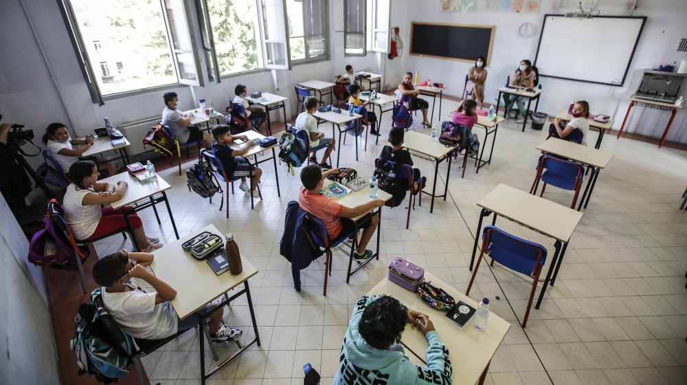 Students sit in their classroom at the San Biagio primary school in Codogno, Italy, Monday, Sept. 14, 2020. The morning bell Monday marks the first entrance to the classroom for the children of Codogn