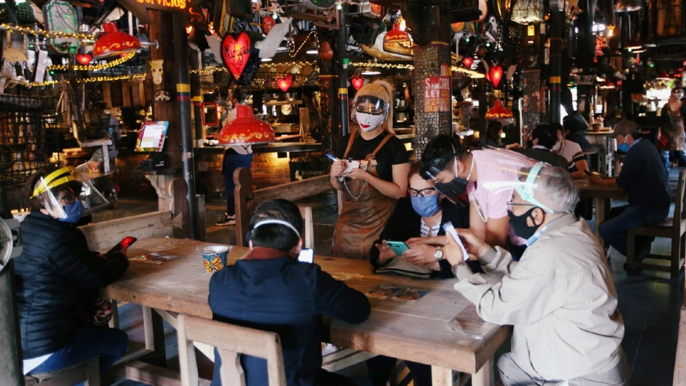 Customers wearing protective masks talk to a waiter at the Andres Carne de Res restaurant, amidst the coronavirus disease (COVID-19) outbreak, in Chia, Colombia August 30, 2020. Picture