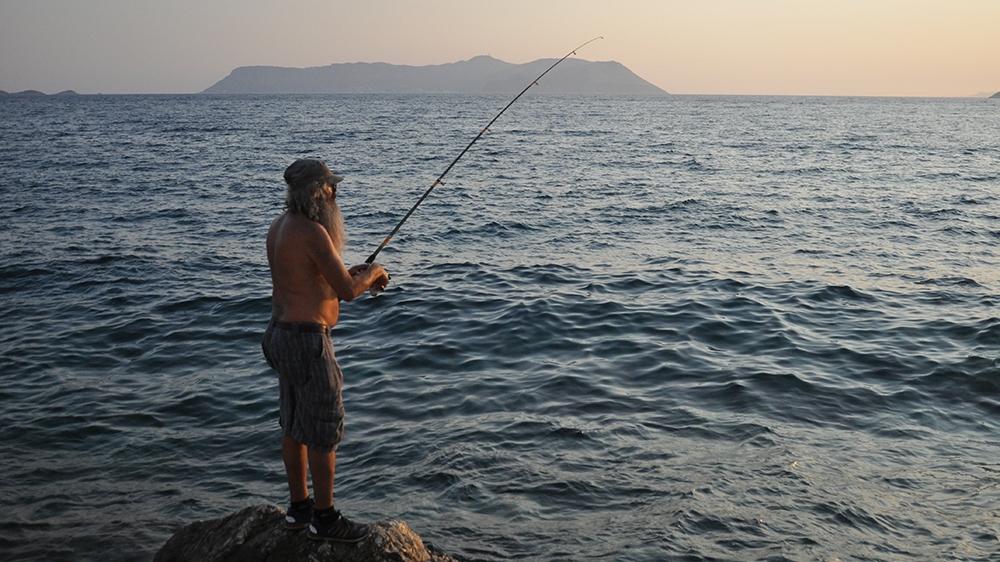 Man fishes in Kas, with Meis in background [Samuel Kent/Al Jazeera]