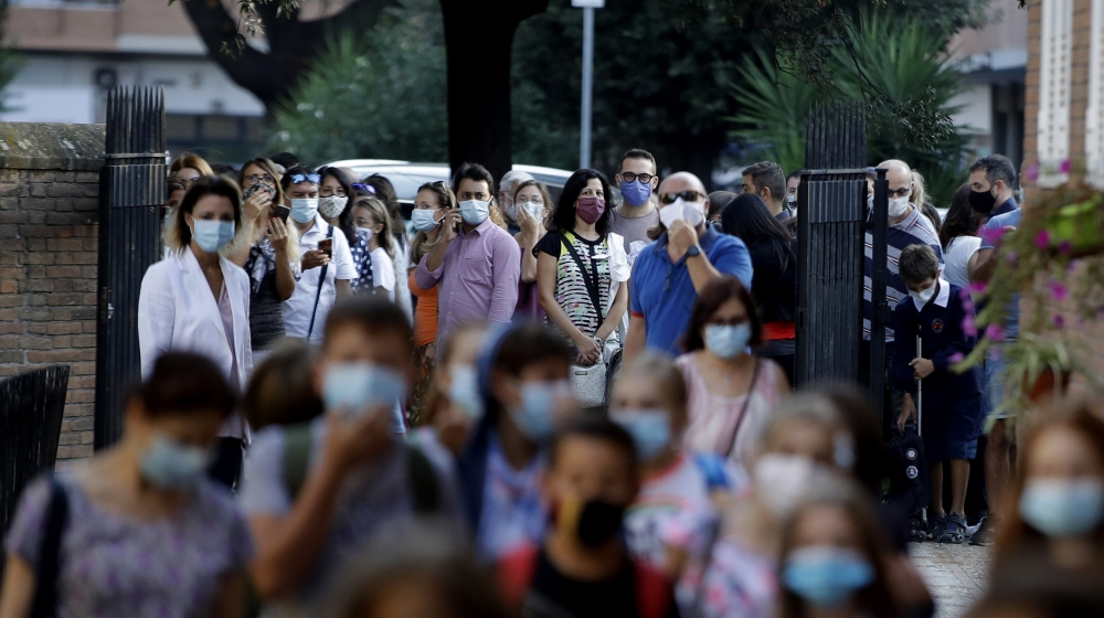 Relatives and parents look at students entering the San Policarpo parish as Italian schools reopened, in Rome, Monday, Sept. 14, 2020. Primary school