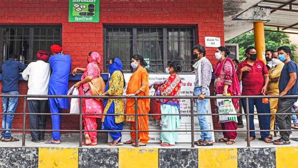 Las personas hacen cola mientras esperan su turno para recopilar informes de prueba para el coronavirus COVID-19, en un hospital civil en Amritsar el 17 de julio de 2020. Los casos de coronavirus en India superaron el millón