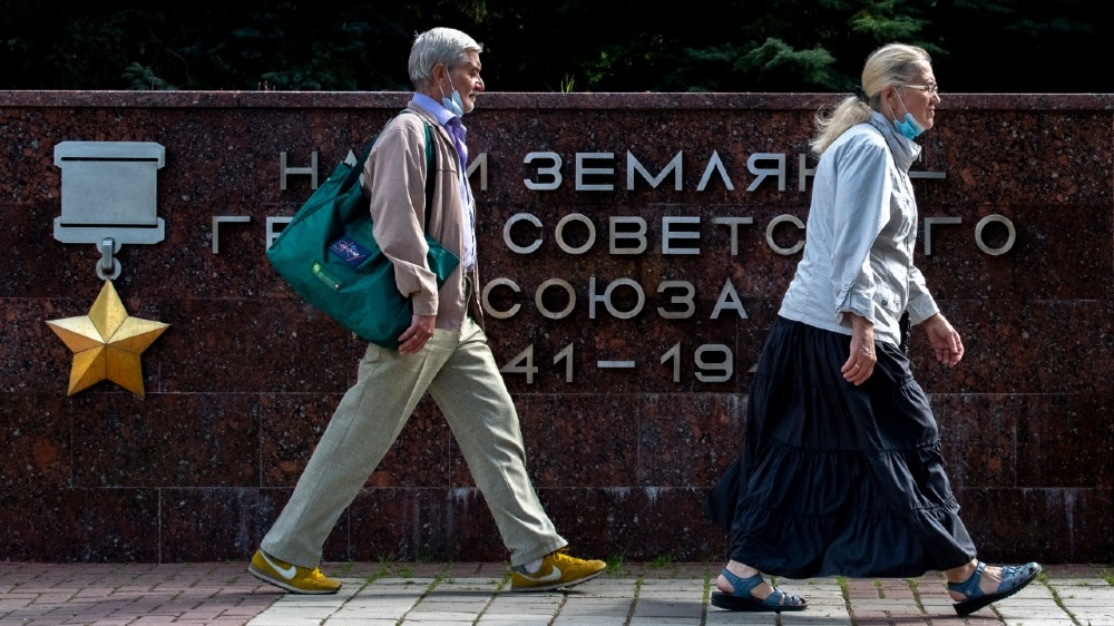 A woman and a man wearing face masks to protect against the coronavirus disease walk past a WWII monument in the town of Chekhov, some 70 km outside Moscow, on August 27, 2020. Yuri KADOBNOV / AFP