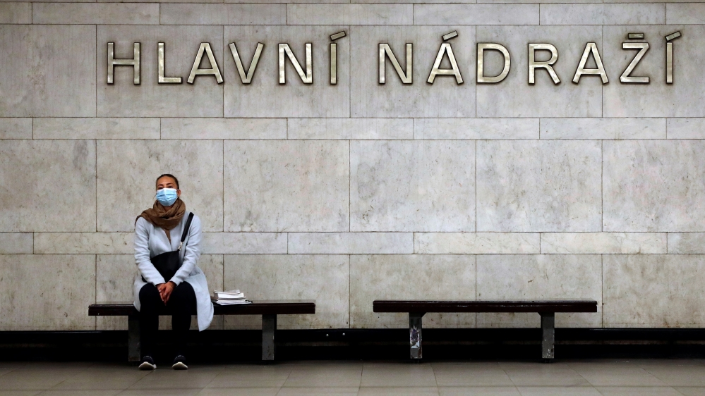 A commuter wearing a protective mask waits for a subway train in Prague