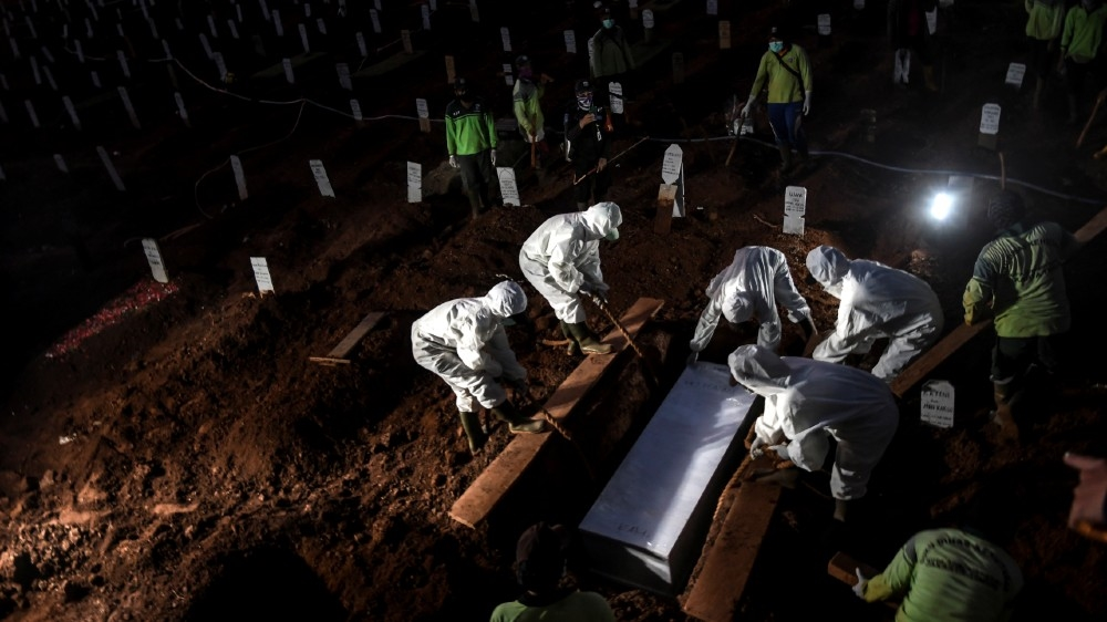 Workers wearing protective suits bury a coronavirus disease (COVID-19) victim at Pondok Ranggon cemetery complex in Jakarta, Indonesia, September 8, 2020 in this photo taken by Antara Foto.