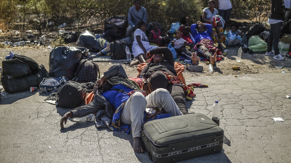 Migrants sleep on the ground outside camp of Moria on the island of Lesbos after a major fire broke out, on September 9, 2020. Thousands of asylum seekers on the Greek island of Lesbos fled for their