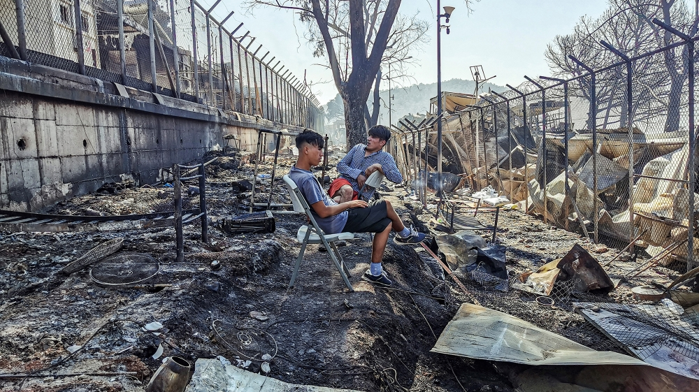 Migrants sit inside the burnt Moria Camp on the Greek island of Lesbos on September 9, 2020, after a major fire. Thousands of asylum seekers on the Greek island of Lesbos fled for their lives early Se