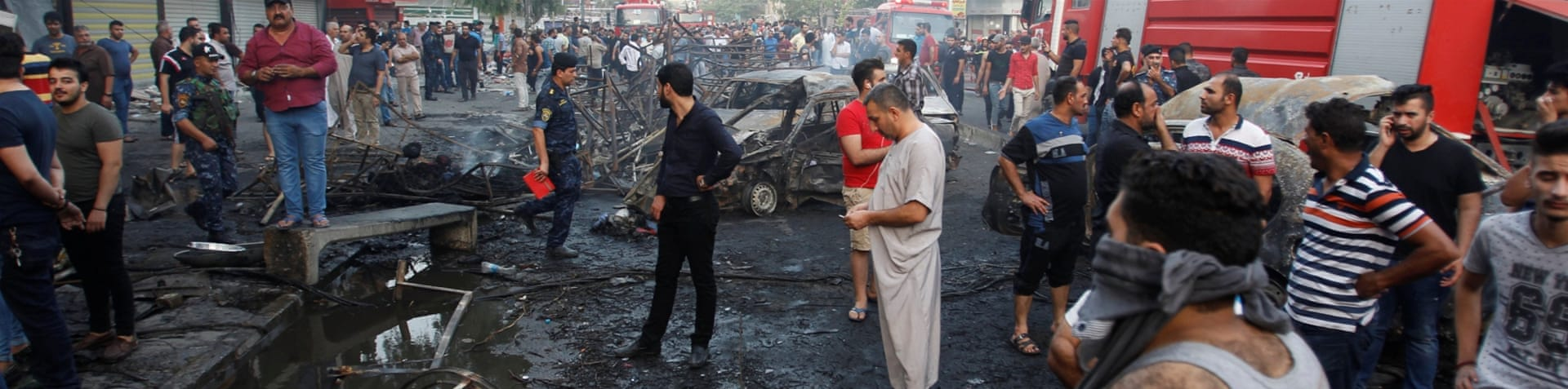 People gather at the site of a suicide car bomb in the Karada shopping area, in Baghdad [Khalid al Mousily/Reuters]