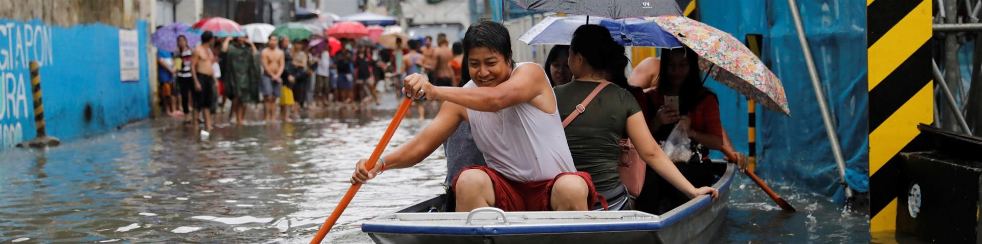 Commuters ride on a pedicab through floodwaters in Las Pinas, Metro Manila as a storm sweeps across the main Luzon island [Erik De Castro/Reuters]