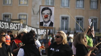 Protestors vent their frustration during a rally on October 5 with a defaced portrait of Prime Minister Coelho [Reuters]