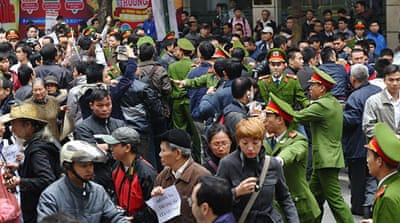 "Protesters carried banners bearing the slogan ""China's military expansion threatens world peace and security"" [Reuters]"
