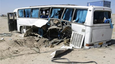 The wreckage of a bus that was damaged in a roadside bomb blast sits beside a road in Ghazni [Reuters]