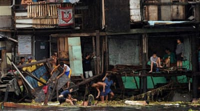 More than a dozen shanty houses in Manila bay were destroyed when the typhoon slammed ashore two barges [AFP]