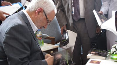 "Ghannouchi signs his latest book, ""Democracy and Human Rights in Islam"" [Yasmine Ryan/Al Jazeera]"