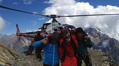 Rescuers assist foreign climbers injured in an avalance at the Mount Manaslu base camp in Gorkha District [AFP]