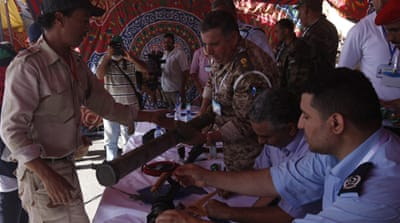 Hundreds of Libyans handed over weapons to the military in Tripoli, Benghazi and other major cities [AFP]