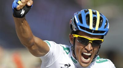 Not even a nearby runner could keep the smile of Contador's face as he takes lead of Tour [Reuters]