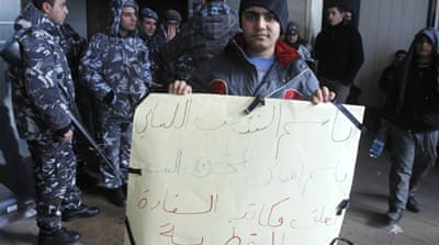 A relative of one of the nine remaining hostages holds a sign reading 'boycotting Turkey and its interests' [EPA]