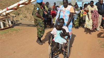 Civilians arrive at UN compound near Juba International Airport to take refuge from fighting [AP]