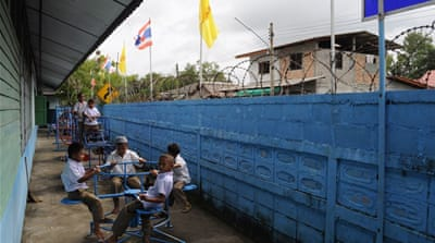 Six soldiers with M16 assault rifles sit around the corridors of Ban Ba Ngo school [Joe Jackson/Al Jazeera]