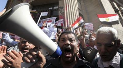 "An anti-Morsi demonstrator holds pans reading, ""Mubarak - Mursi"" during a protest in Cairo [Reuters]"