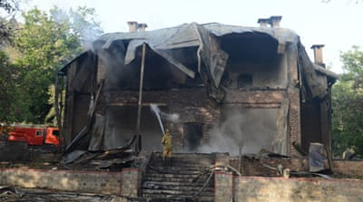 A policeman was killed and the ensuing blaze tore through the two-storey wooden building [AFP]