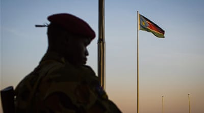 A South Sudanese government soldier stands guard as the country's flag flies in the background [AP]