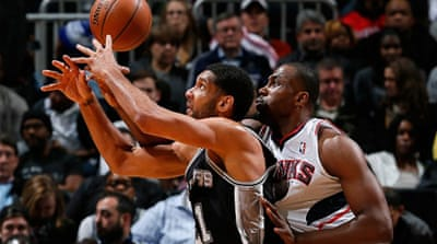Elton Brand of the Atlanta Hawks fouls Tim Duncan of the San Antonio Spurs at Philips Arena [AFP]