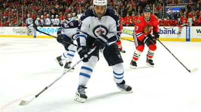 Jets defenseman Dustin Byfuglien is pursued byBlackhawks defenseman Brent Seabrook [Reuters]