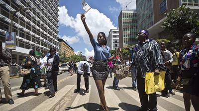 Women and men march to protest the stripping of a woman for wearing a miniskirt [Emily H Johnson/Al Jazeera]