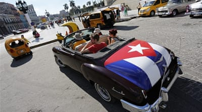 "A woman with a poster of the Cuban Five, which reads in Spanish ""Freedom Now,"" celebrates their release [AP]"
