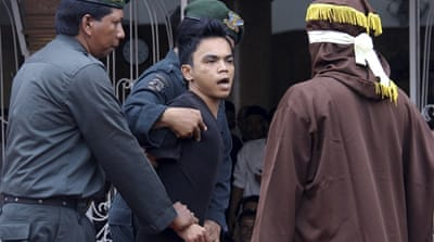 An Islamic law official whips a man convicted of gambling with a rattan cane inside a mosque compound [AP]