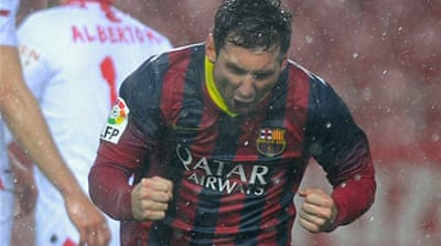 Lionel Messi celebrates in the rain-drenched Ramon Sanchez Pizjuan stadium, Sevilla [AFP]