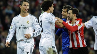 Cristiano Ronaldo walks off as teammates argue with Athletic players following the forward's red card [AFP]