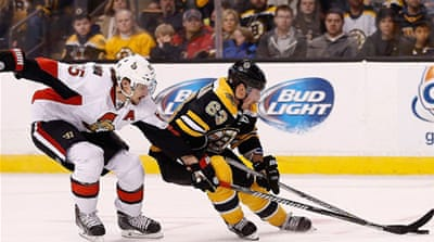 Brad Marchand of the Boston Bruins gets checked by Erik Karlsson of the Ottawa Senators [AFP]