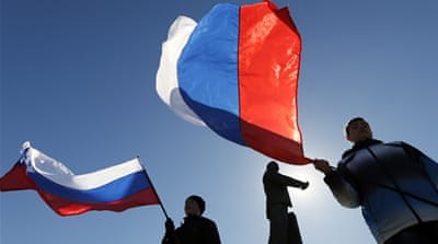 People hold Russian flags as they celebrate the results of the referendum on Crimea's status at the central square [EPA]