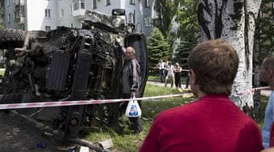 Ukrainians gather around a wrecked army truck in Donetsk [John Wendle/Al Jazeera]