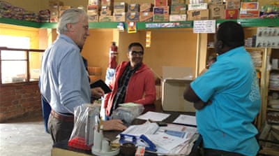 Simon Berry and Rohit Ramchandani speak to a shop owner about their life-saving product in Katete, Zambia [SIMON BERRY]