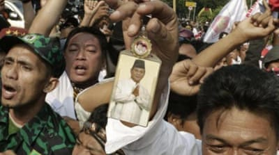 A supporter holds a portrait of losing presidential candidate Prabowo Subianto during a protest near the Constitutional Court in Jakarta, Indonesia [AP]