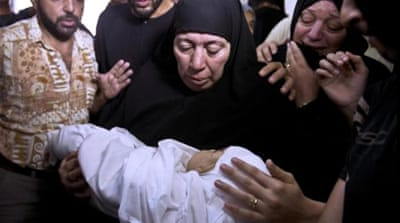 Relatives of seven-month-old Ali Deif hold his body as they mourn during the funeral of both the child and his mother in Jabalia, in the northern Gaza Strip [AFP]