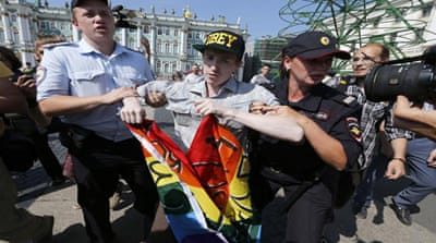Gay activists beaten by anti-gay protesters during a homosexual rights rally in St Petersburg [AP]