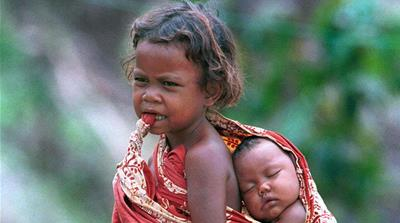An Orang Asli child carries her brother on her back in a village 400km north of Kuala Lumpur, Malaysia [Teh Eng Koon/AP]