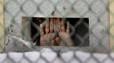 A detainee shields his face as he peers out through a 'bean hole', which is used to pass food and other items to detainees at the Guantanamo Bay naval base [File: Brennan Linsley/AP Photo]